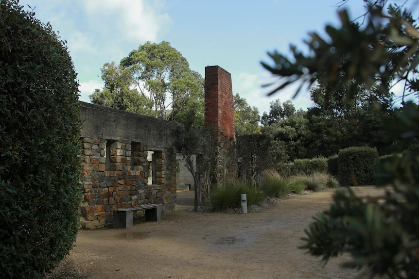 A brick fire place stands in ruins of a building