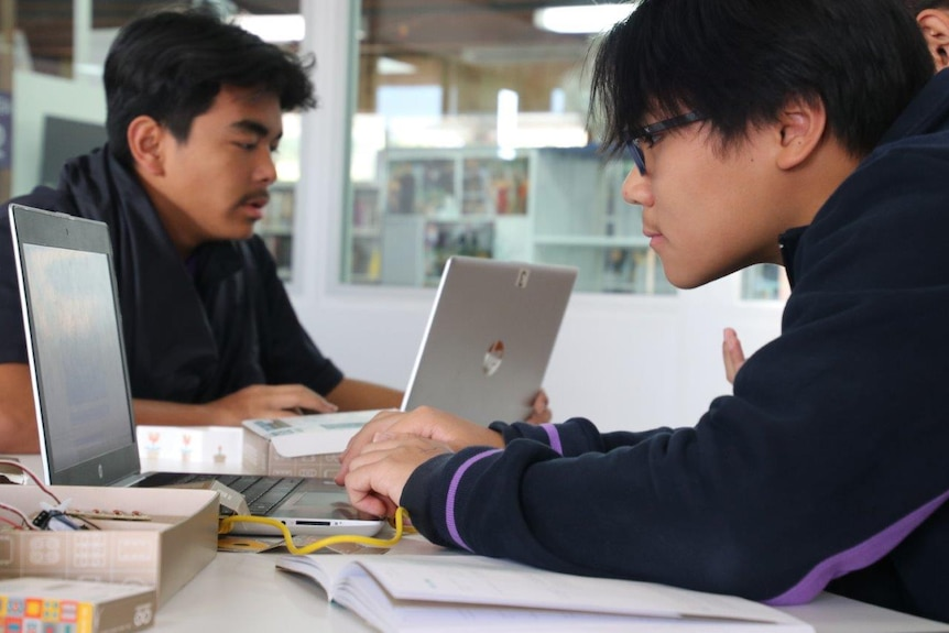 Two boys facing opposite each other working on computers at a school desk.