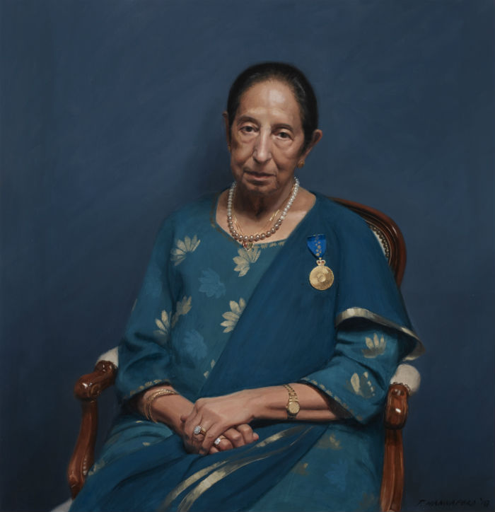 A older woman wearing a blue and aqua sari sits in a wooden arm chair in front of a blue wall.