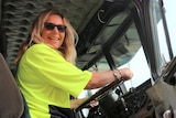 A woman with long blond hair sits in the drivers seat of a truck and smiles