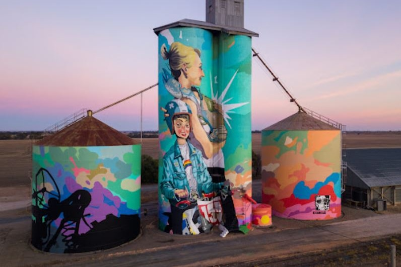 Four silos are painted in bright colours with images reflecting farm life