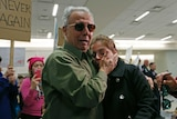 An Iranian green card holder cries on the shoulders of her father after being released at Dallas airport