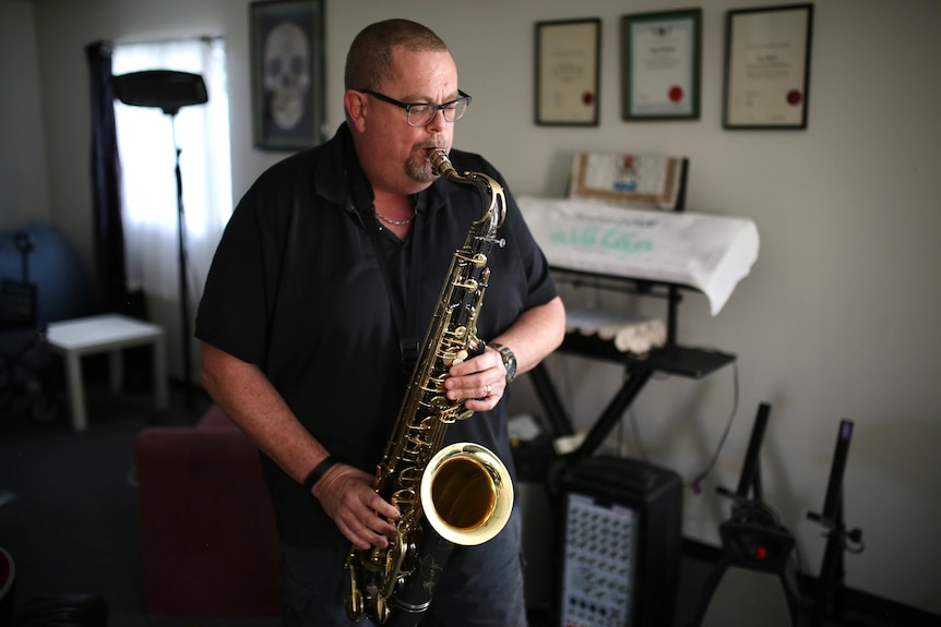 Andrew wears a black tshirt playing a saxophone in a music room in a suburban house.