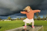 A child in a peach coloured cardigan plays on a stone bench with storm clouds overhead.