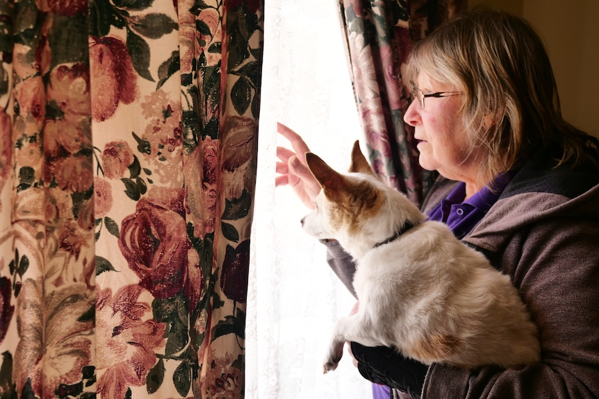 A woman holding a little dog looks out a window.