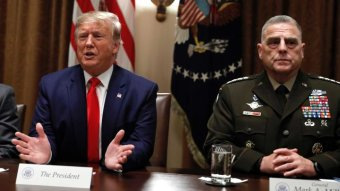 Donald Trump speaks as the Chairman of the Joint Chiefs of Staff, General Mark Milley (right), listens.