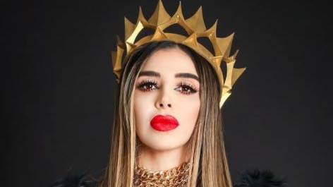 Brunette woman with full, red lips wears black jacket and gold crown