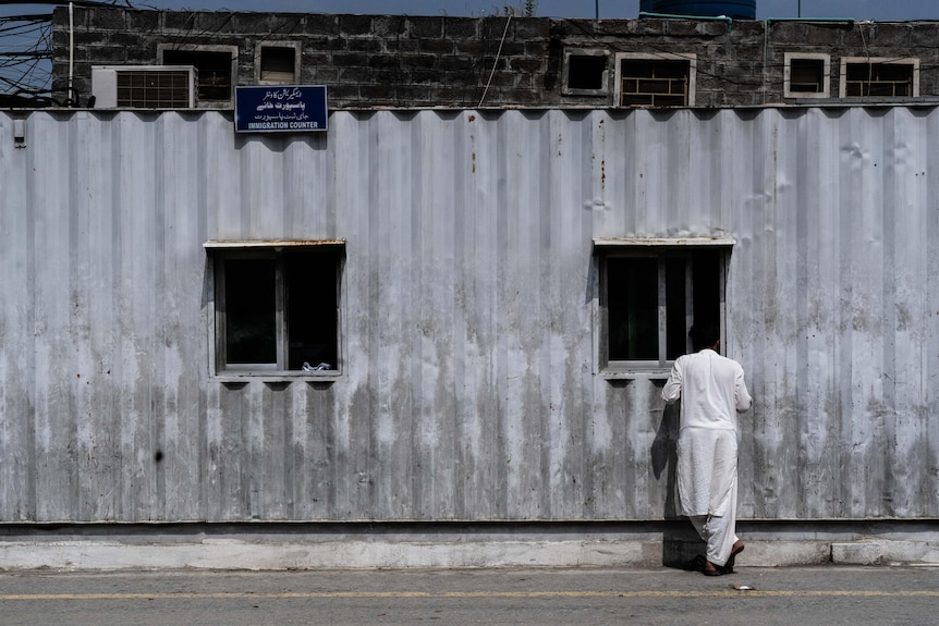 A man stands at a window of a corrugated iron building with a sign reading 'immigration'