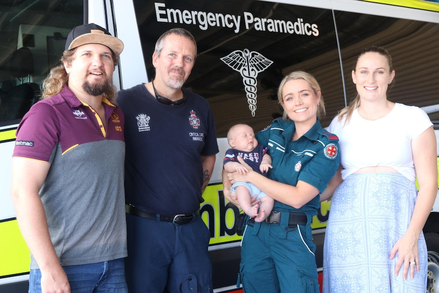 A group of four people in front of an ambulance, holding a baby.