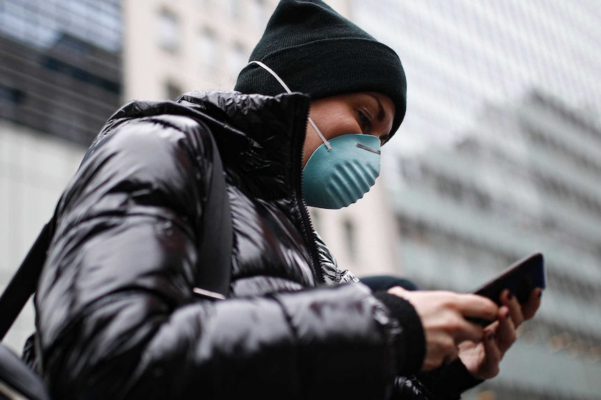 A woman in a black jacket wearing a dark beanie and a green face mask looks at her mobile phone.