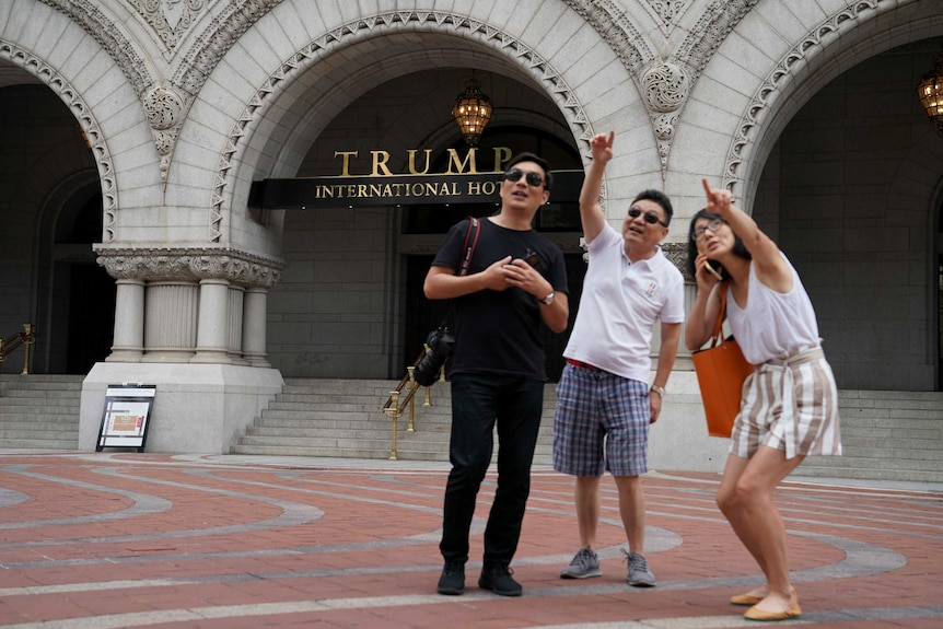 A group of people point to a person in a window of a building across the street while standing in front of the Trump Hotel