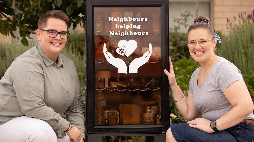 Two women kneel either side of a pantry box filled with food that says 'Neighbours helping neighbours'.