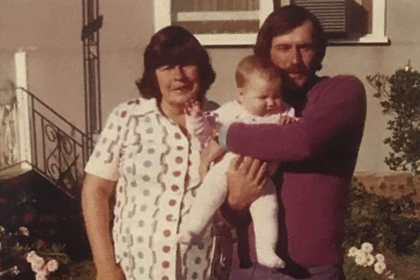 An older woman standing with a younger man who is holding a small baby on the front lawn of a house.