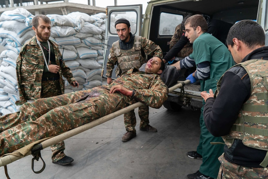 A soldier lies on a stretcher with blood on his face as other men put him in a truck