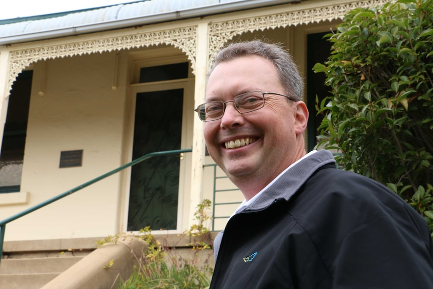 Bathurst's Chifley Home museum coordinator Ben O'Regan standing in front of Chifley Home smiling.