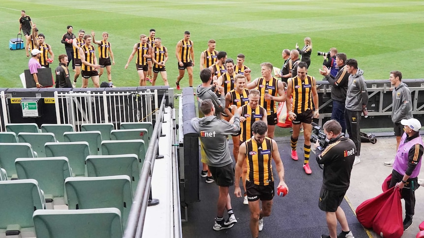 Hawthorn players walk off the MCG and down the race after completing their game against Brisbane.