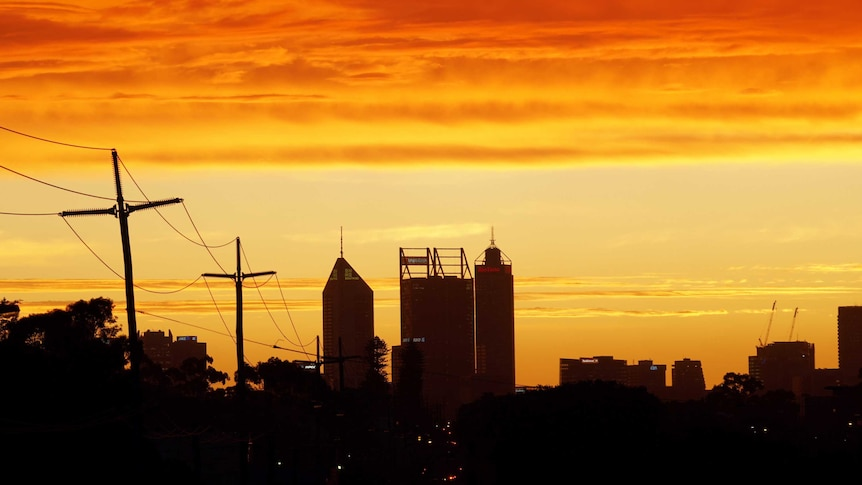 Perth's skyline with a bright orange and yellow sky in the background.