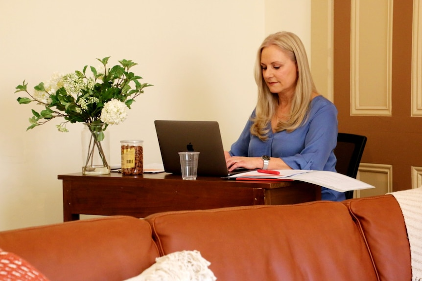 A woman with blonde hair wearing a blue top sits typing at a laptop on a desk next to a vase of flowers.