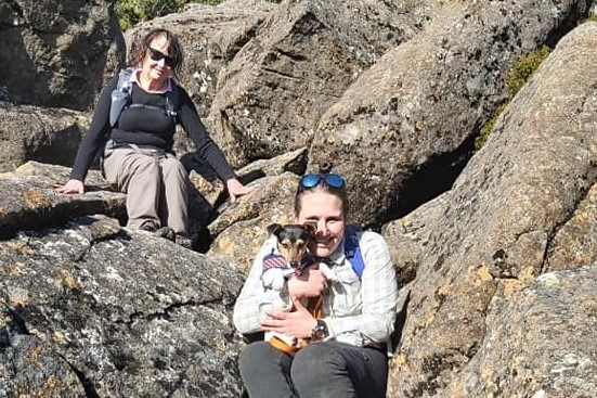 Two women with a small dog climbing a rockface.