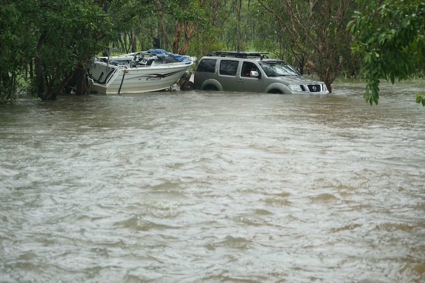 A four wheel drive towing a boat in water.