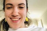 Hannah Diviney smiling selfie while sitting inside in a white room, wearing flower earrings