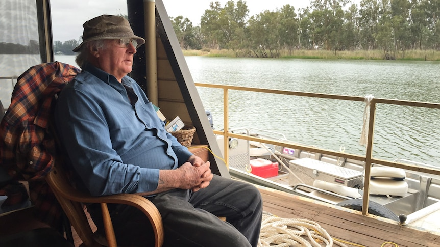 Rodney West sits on a rocking chair on the back deck of his houseboat and looks out at the river.