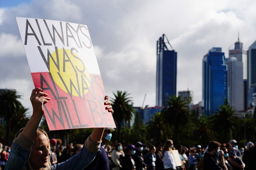 A woman holds up a sign saying 'always was, always will be' at a protest in Perth.