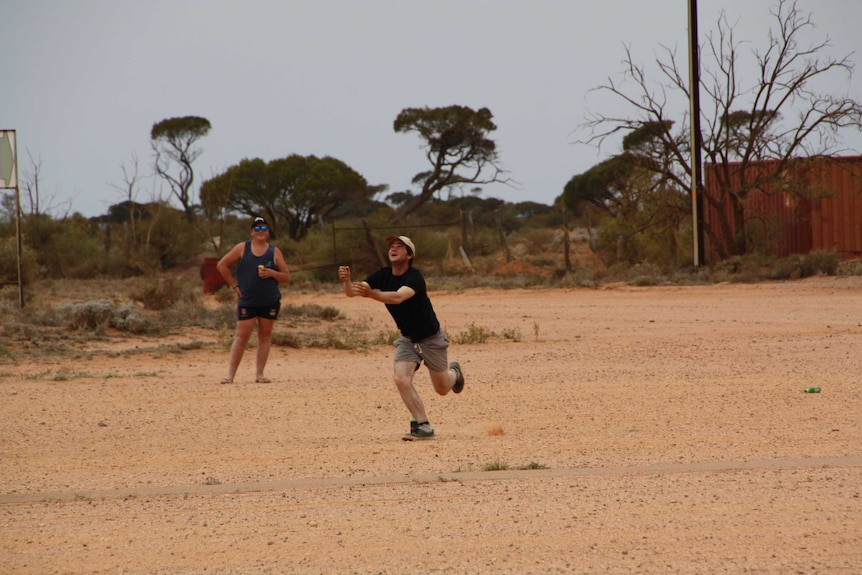 A man in a black shirt and yellow cap runs to catch a falling ball while another man drinks a beer.