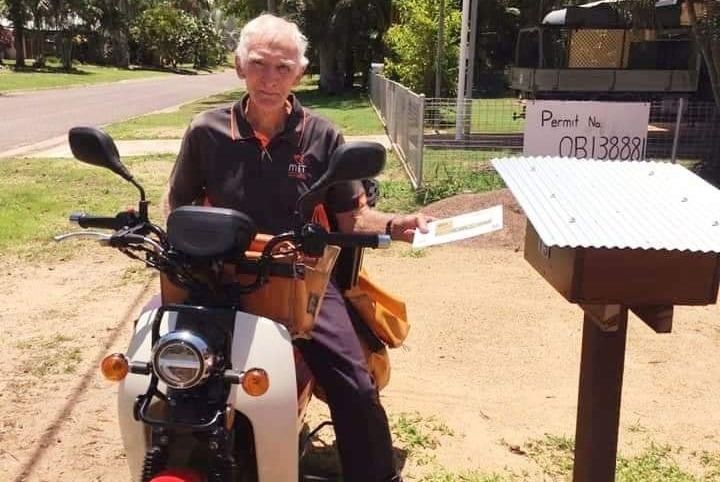 man sits on bike holding envelope in front of mail box