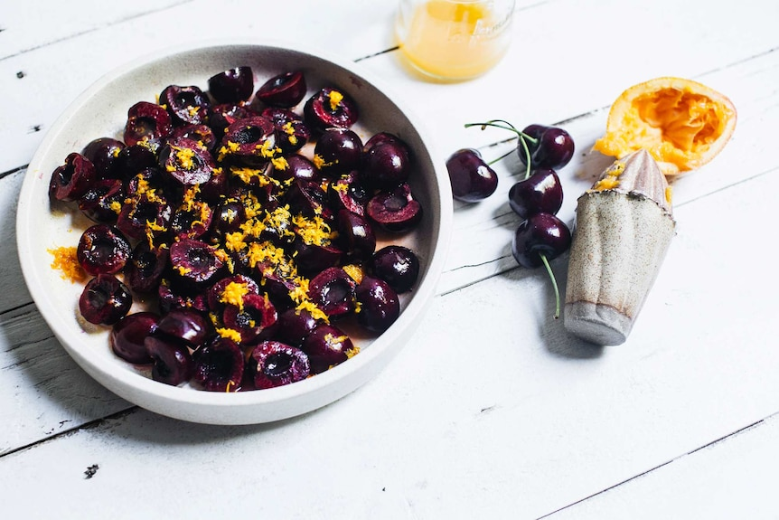 Halved cherries in a bowl with orange zest and juice, half of an easy summer fruit and crumble dessert recipe.