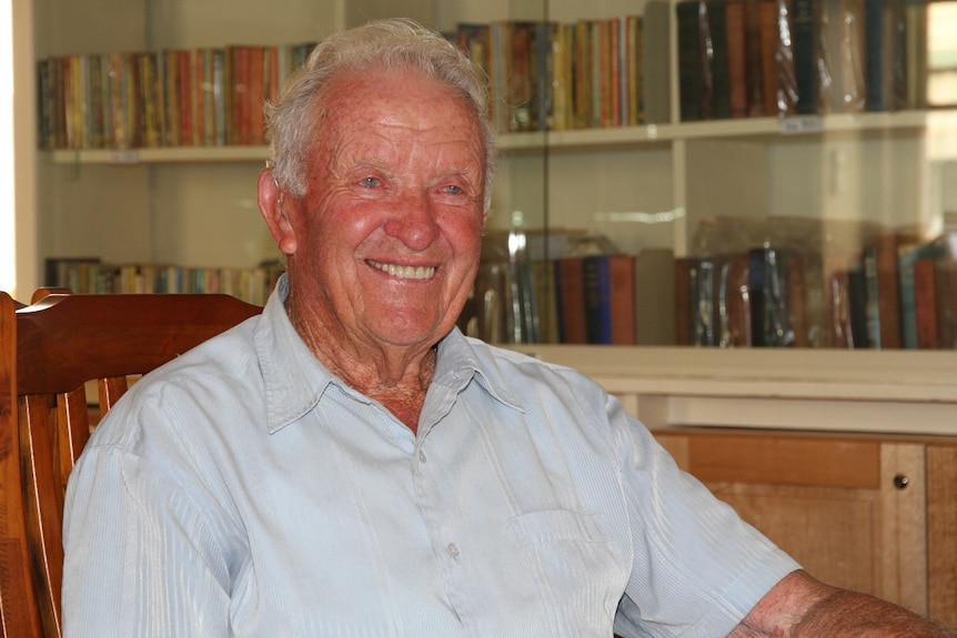 An elderly man in a house, bookshelves behind him, looking off-camera and smiling.