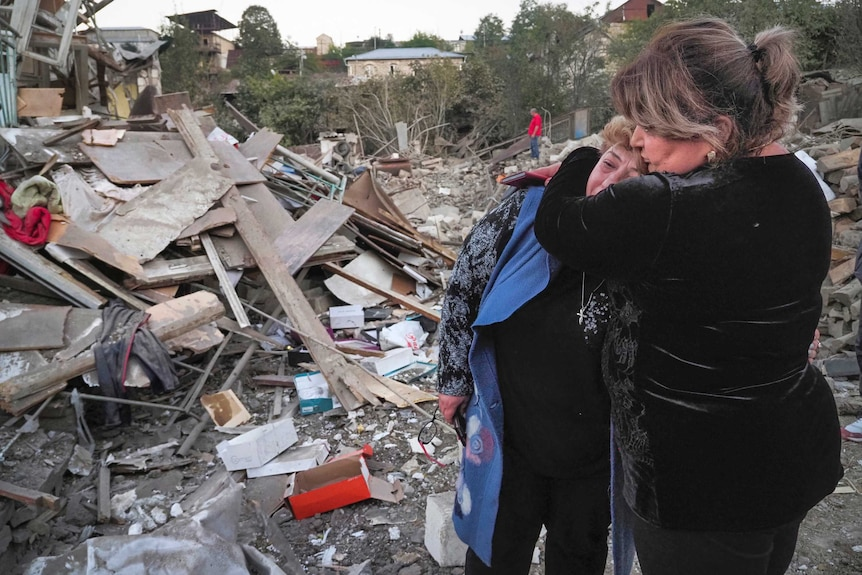 A neighbour comforts home owner Lida Sarksyan near her house, which was destroyed by shelling from Azerbaijan's artillery.