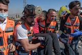 Paramedics carry an injured man in the West Bank