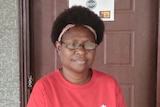 Head-shot of a Papua New Guinean woman in a red shirt