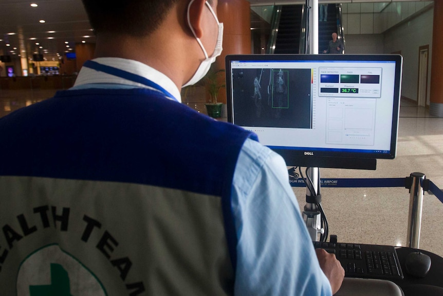 An airport staff member reads a computer screen to check the body temperatures of passengers.