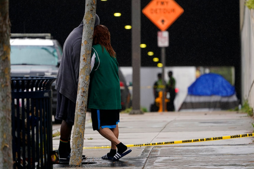 A woman and man stand at the scene of a deadly accident, in San Diego with tents in the background.