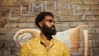 Heritier Lumumba stands in front of a wall with a mural painted on it of Patrice Lumumba.
