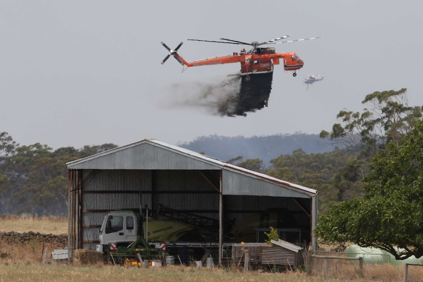 A sky crane helicopter drops retardant on a small building at Claredon, Victoria