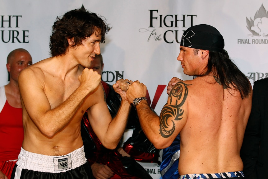A shirtless Justin Trudeau poses with his fists up next to a shirtless Patrick Brazeau