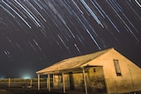 A long exposure leaves star trails in the night sky above a shed in a field on a rural property.