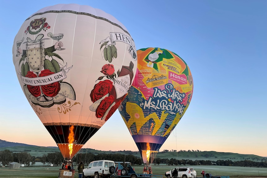 Two hot air balloons sit side by side on the ground