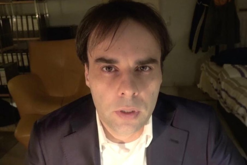 A dark-haired middle age man stares directly into the camera.