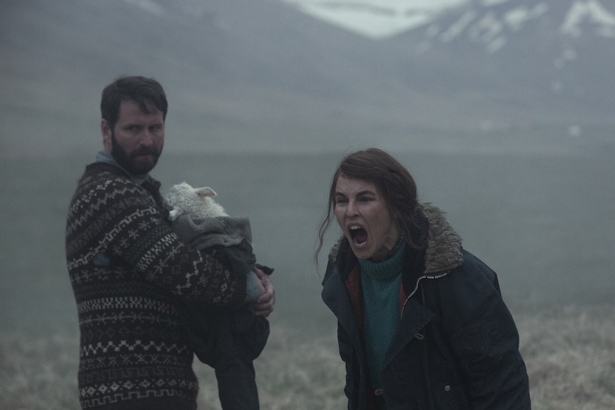 Bearded man in a patterned knitted jumper clutches a lamb to his chest while dark-haired woman in rugged blue jacket yells.