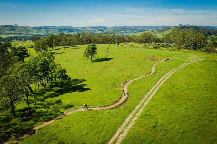 An aerial view of the Dungog Common showing the bike track cutting through lush green hills