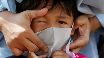 An Indonesian child has a protective face mask adjusted.