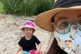 Woman wearing a mask takes a selfie with a child in a sandpit.