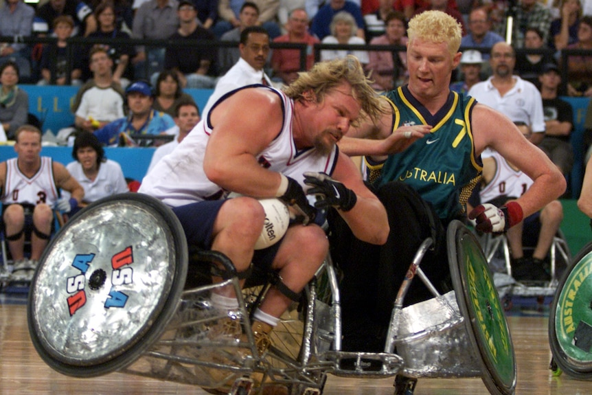 Two Paralympic wheelchair rugby players brace as their wheelchairs collide on court during the gold medal game.