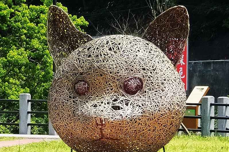A giant twine cat head watches over a street path.