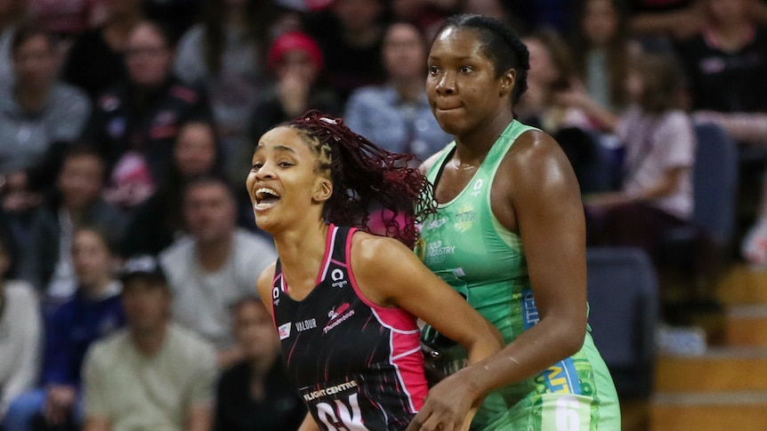 An Adelaide Thunderbirds Super Netball player leans against a West Coast Fever opponent.