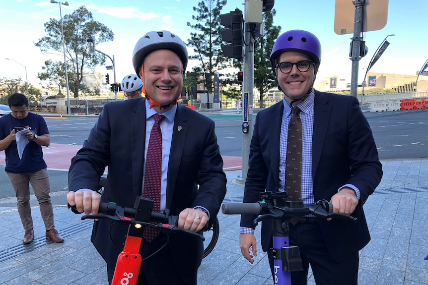 Two men wearing helmets smiling while holding e-scooters.